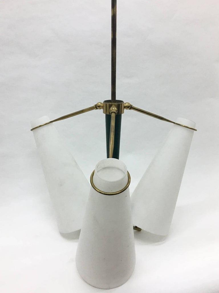 Three-light chandelier in the style of Stilnovo with articulated brass arms, green metal central part and white glasses. Fully restored electrical parts. It works with both 110 and 220 Volt and needs regular e14 bulbs