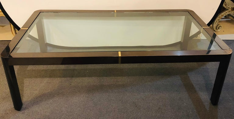 A modern coffee/low table. Brass, metal and glass. This fine Hollywood Regency style metal coffee table has hidden glass supports on a brass and metal frame.