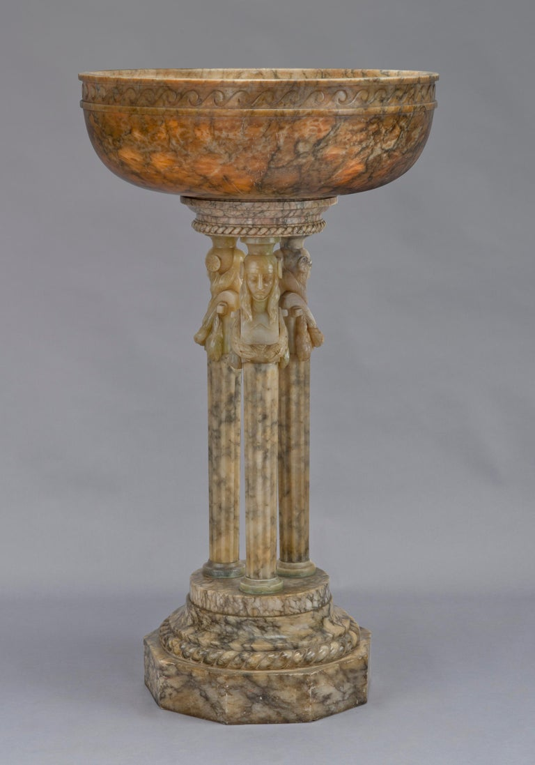 A monumental alabaster figural jardinière.  Italian, circa 1930.   This large and impressive alabaster jardinière has a deep basin finely carved with a border of vitruvian scroll and raised on three columns headed by beautifully carved herm