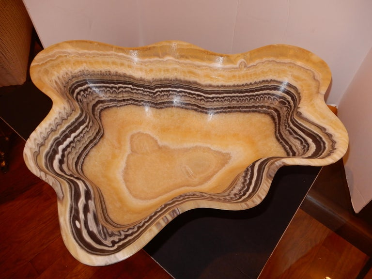 One of a kind artisan crafted onyx bowl. Please click through as there are multiple images, showing the vessel from many views, the colors and natural patterns are exquisite. When placing a small light in the center the bowl it becomes totally