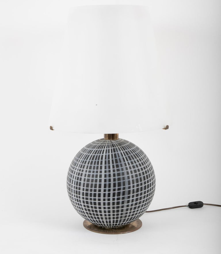 A lamp constructed of a striking black and white grid sphere with a brass armature supporting a white frosted glass shade / diffuser. Made by La Murrina, circa 1970s.