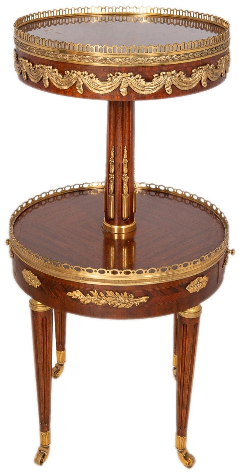 A good quality near pair of French Louis XVI style Mahogany two-tier circular side tables, each with gilded ormolu mounts, galleries to both tiers, a frieze drawer and raised on turned tapering fluted legs terminating in brass castors.