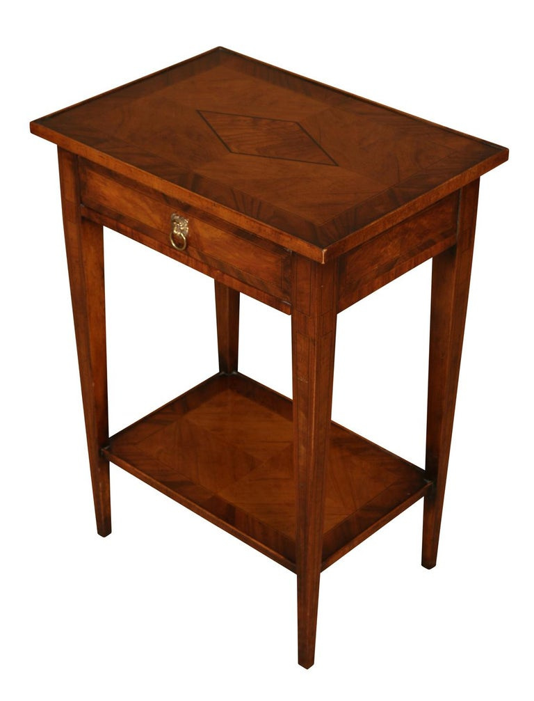 A nice looking little table in walnut with lovely cross banding detailing and an inlaid design on top. This useful little table features a single drawer with a lion's head ring pull and a lower shelf.