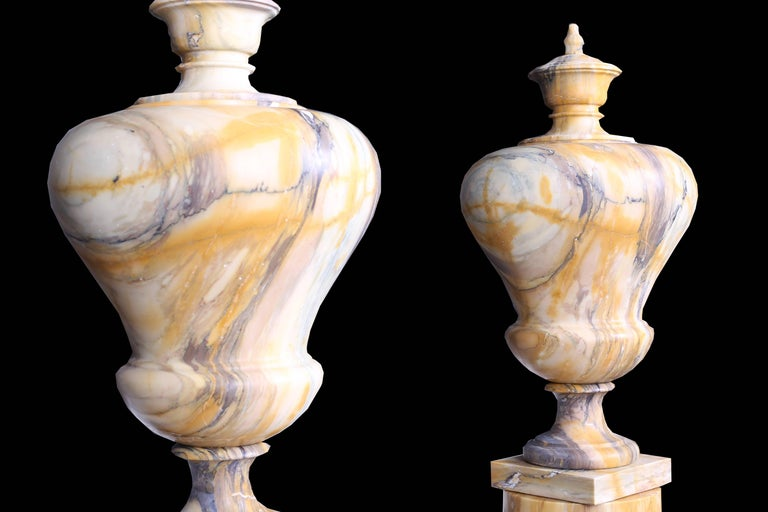 A pair of neoclassical style vintage rather grand extremely tall urns in high quality Sienna and early 20th century, raised on high quality Sienna marble column plinths with Pavonazzo marble bases, Italian, circa 1920.  Measurements: Depth 16