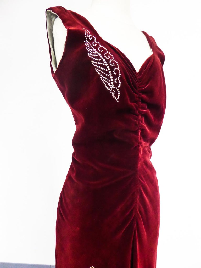 Circa 1935 France  Rare long collector's evening dress, French Haute Couture by Nicole Groult, famous sister of Paul Poiret and dating from the 1935s. Sleeveless dress in carmine red silk velvet underlined with Swarovski rhinestone embroidery with
