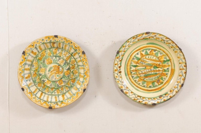 A pair of Spanish Majolica platters in bird and leaf motif from the 18th century. This pair of antique Majolica platters from Spain, each glazed in beautiful jewel tone colors typical of Majolica style. The dominant coloring of this pair of plates