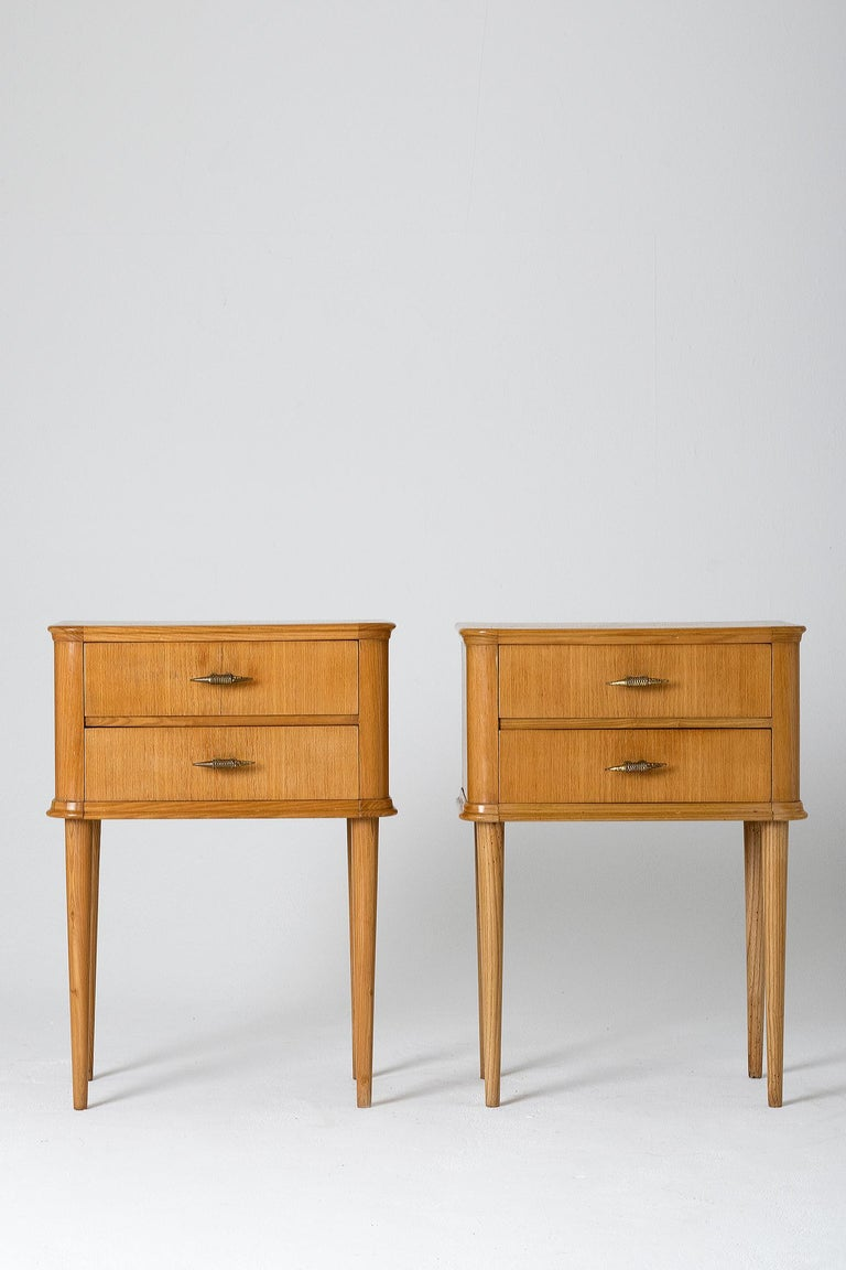 A pair of oak bedside tables, the two drawers with unusual brass handles resting on four tapered legs. Italy, circa 1940.