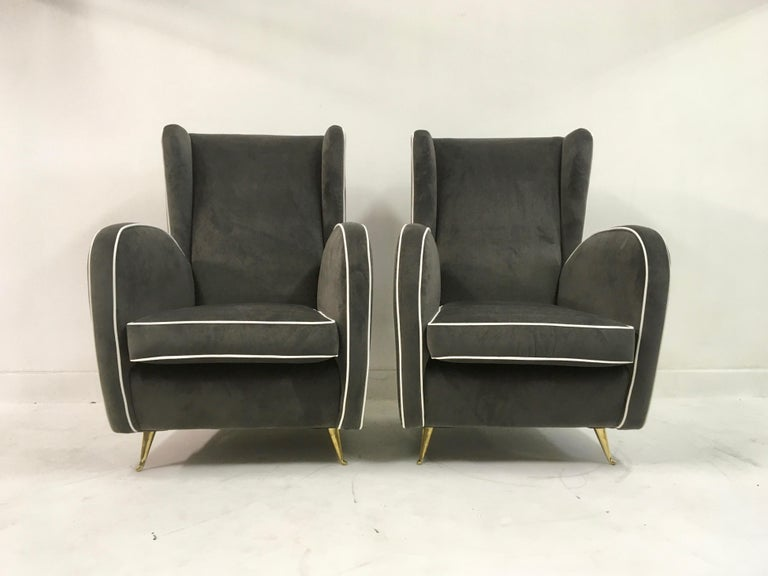 A pair of armchairs  On brass legs  Grey velvet  White piping  High back  Italy, 1950s.