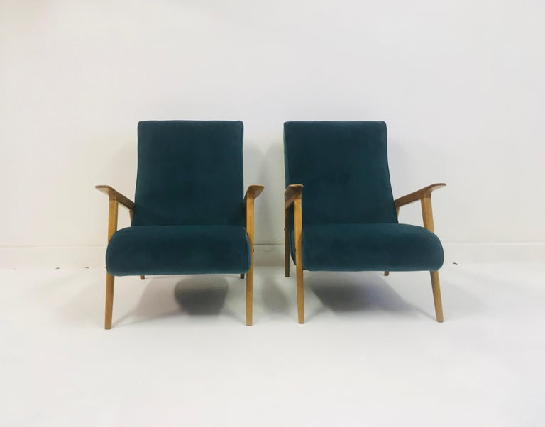 A pair of armchairs  New teal colored velvet upholstery  Refinished frame  Italian, 1950s  Seat height 38cm.