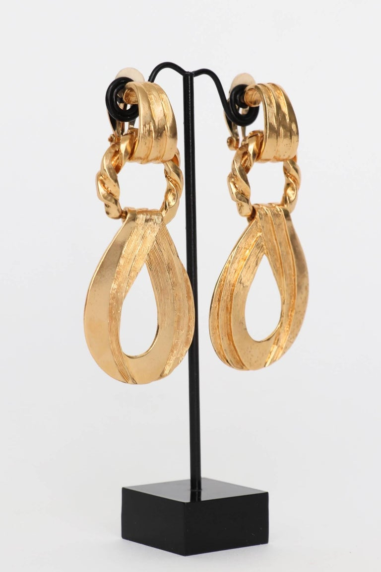An incredible pair of 1980s Yves Saint Laurent gold toned clip-on earrings with a detachable pendant.   The earrings are stamped: YSL