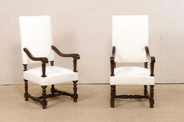 An Italian pair of carved-wood armchairs with newly upholstered fabric from the 19th century. These antique chairs from Italy each have a large rectangular-shaped back, with gracefully carved wooden arms that gently slope and terminate into scrolled