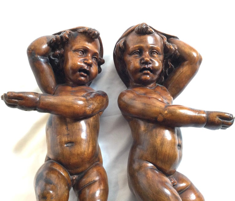 A pair of caved walnut 19th century Italian cherubs with an original warm finish. These were apparently taken from a large piece of furniture or elaborate wood paneled room. Mostly intact with the big toe on each missing.