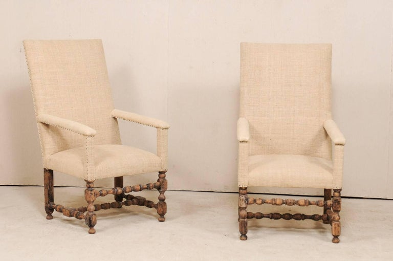 A pair of Italian 19th century upholstered and carved wood arm chairs. This pair of antique Italian armchairs feature tall, rectangular backs with squared crest rail, and nicely turned wood legs. The straight lines are repeated within the arm rest