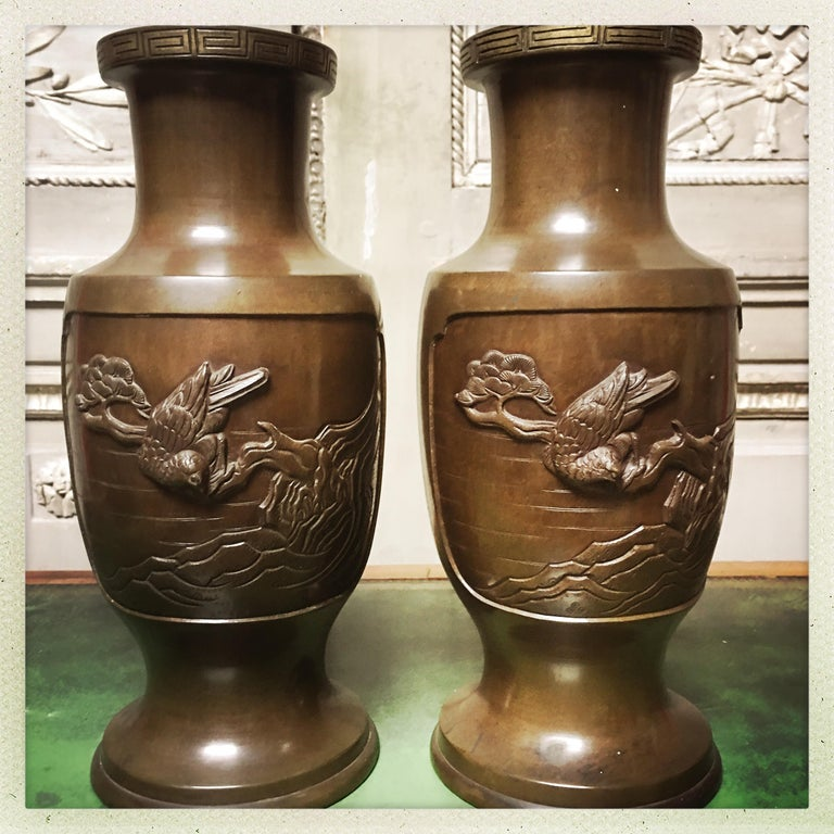 A pair of Japanese bronze vases depicting scenes with different birds. These would make a wonderful pair of lamps.