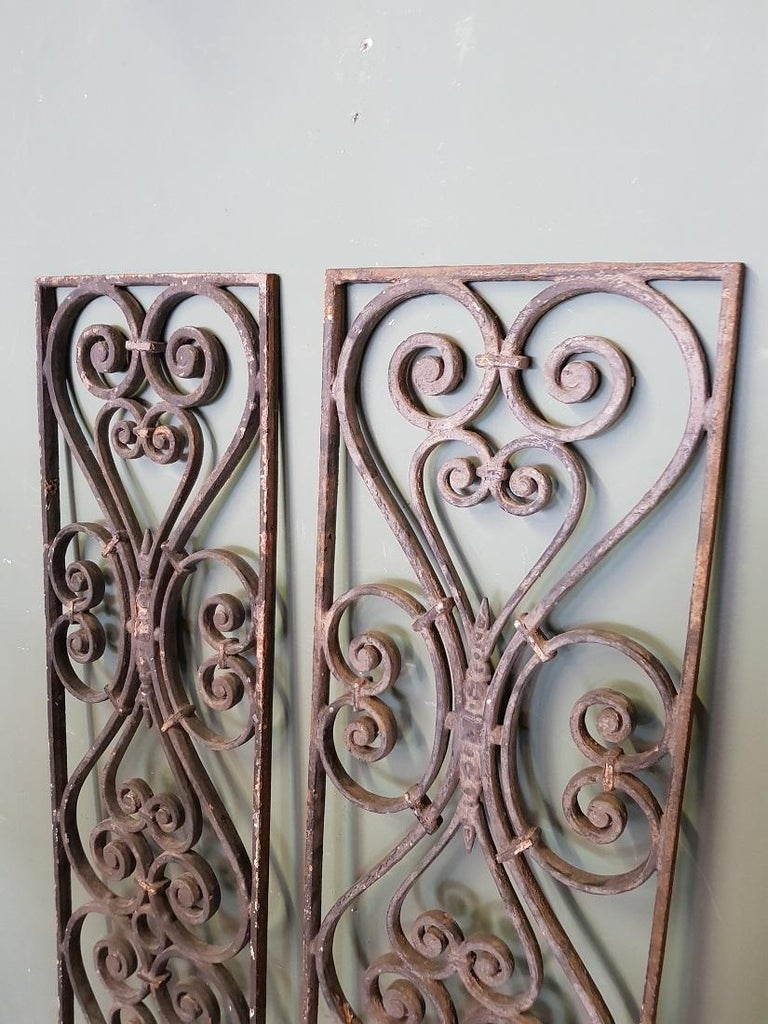 A pair of 2 identical old French cast iron door grilles decorated with various curled elements, these are both in a good but used condition. Originating from the first half of the 20th century.  The measurements are, Depth 2 cm/ 0.7 inch. Width