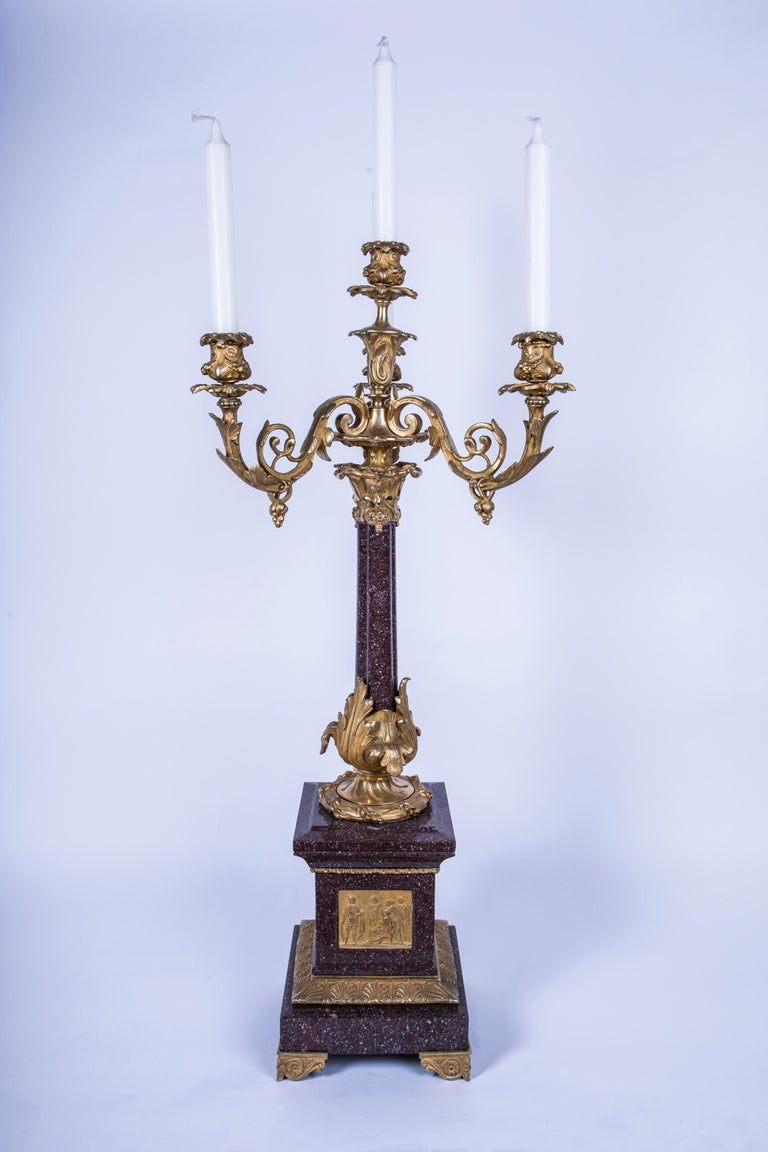 A 4-candle (three-branch and one centre arm) foliate candelabra comprised of a porphyry marble column mounted on porphyry and bronze decorated plinth base with front facing Roman figure ormolu relief, all standing on 4 bronze decorative