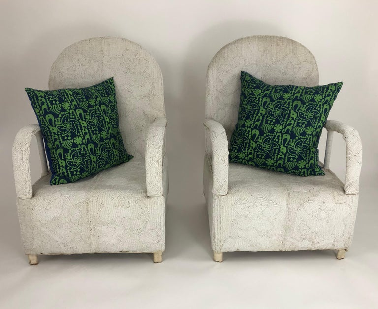 A pair of beautifully handmade African beaded lounge chairs by the Yoruba People, Nigeria. Originally reserved for Yoruba Royalty, these sculptural and comfortable chairs are decorated overall with small white beads. Completely handmade, these