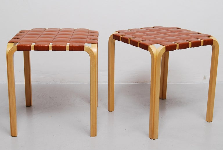 Designed in 1947, Alvar Aalto's Y61 stool required a special technique to create the unique birch Y-legs. This pair with original leather seats are in a wonderful condition. Manufactured by Artek.