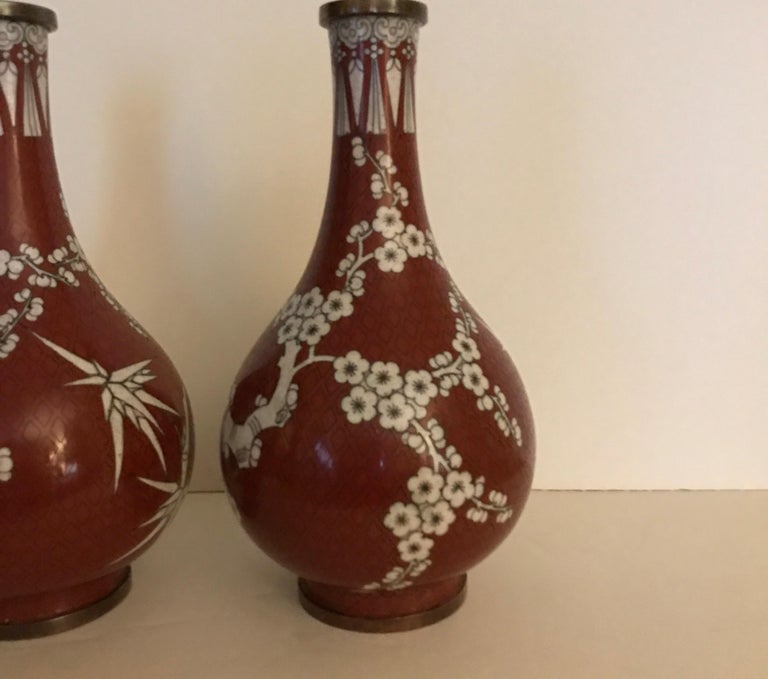 A pair of Chinese Cloisonne vases in cinnabar and white color. The gord form with slim taper neck and bulbous body. The pattern is cherry blossom with bamboo branches.... Antique Chinese, circa 1900.