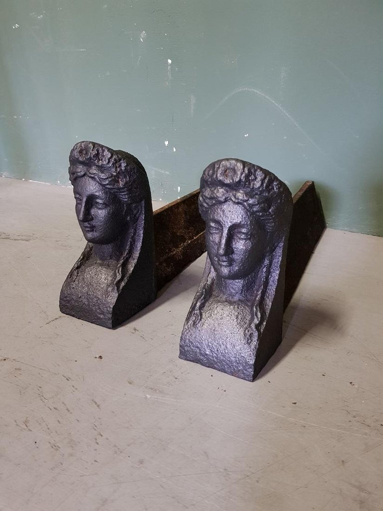 Set French antique cast-iron fire-goats on which the logs are laid in the fireplace, both have a woman's head at the front for decoration, both are in good but used condition. Originating from the second half of the 19th century.