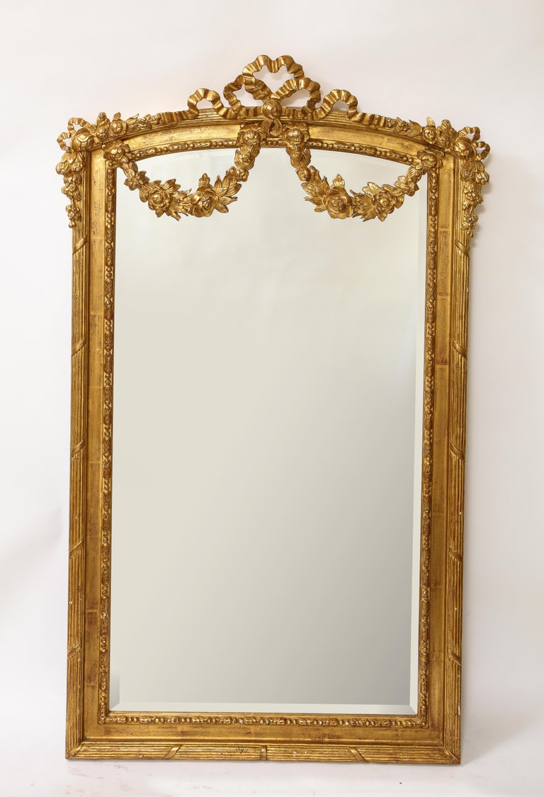 A fabulous pair of antique French Louis XVI style hand carved giltwood mirrors. Each is beautifully modeled in hand carved wood with garlands and flowers of ribbons and further enhanced with 24-karat original two-tone matte and burnished water