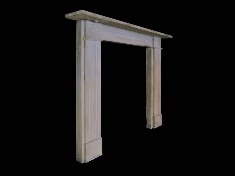 A pair of Regency English stone fireplaces, with carved roundel corner blocks, conforming moulded panels to jambs and frieze. All beneath a simple shelf. One being slightly smaller than the other, early 19th century 