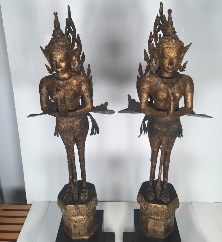 The bronze sculpture with patinated gilt finish with expected age wear. Each with a later black wood base. Thailand, early 20th century, 1920.