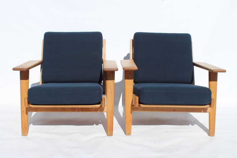 A pair of armchairs, model GE290, designed by Hans J. Wegner and manufactured by GETAMA in the 1960s. The chairs are of oak and cushions of dark blue wool.