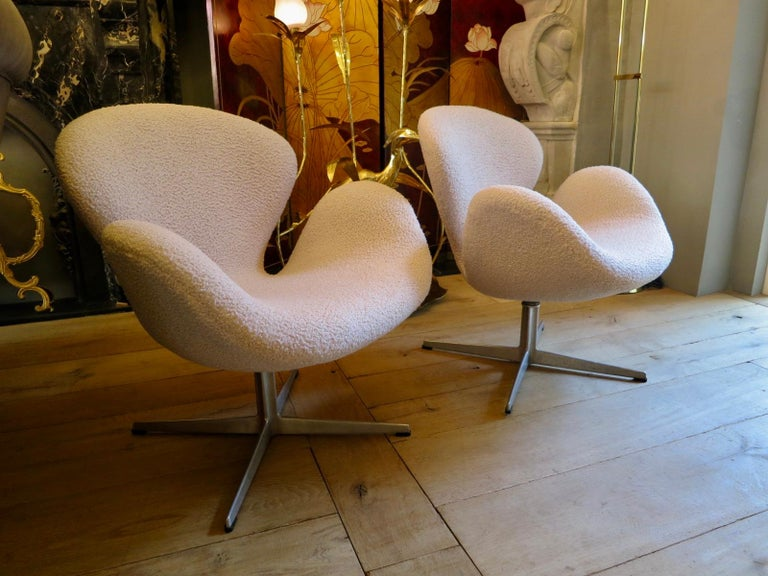A pair of original Arne Jacobsen swan chairs recovered in a bouclé style fabric. Labeled and authentic early pair. Manufactured by Fritz Hansen, Denmark.