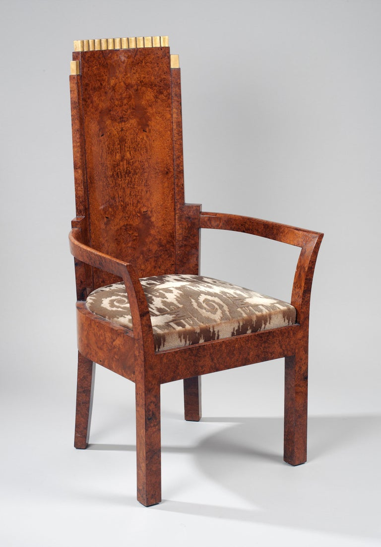 The tops of the curved attenuated backs are fitted with giltwood cappings. The backs and fronts of the high backs are quarter veneered and the arms are curved and shaped around the seat. With square legs and upholstered in a brown patterned