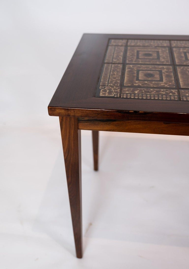 A pair of bedside tables in mahogany with brown tiles of Danish design from the 1960s. The tables are in great vintage condition.