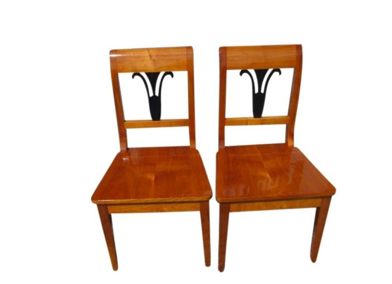 A pair of chairs made in the famous Biedermeier style. The pieces were manufactured after an old template. A massive cherrywood makes up the whole chair and adds the typical color of the cherrywood to the furniture. A black ornament in the rest adds