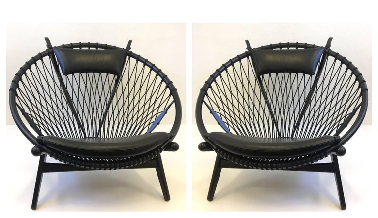 A spectacular pair of PP 130 circle lounge chairs designed by Renowned Danish designer Hans J. Wegner for PP Møbler in the 1980s. This was the last chair designed by Wegner. The chairs are oak lacquered in black, the seats and the headrest are