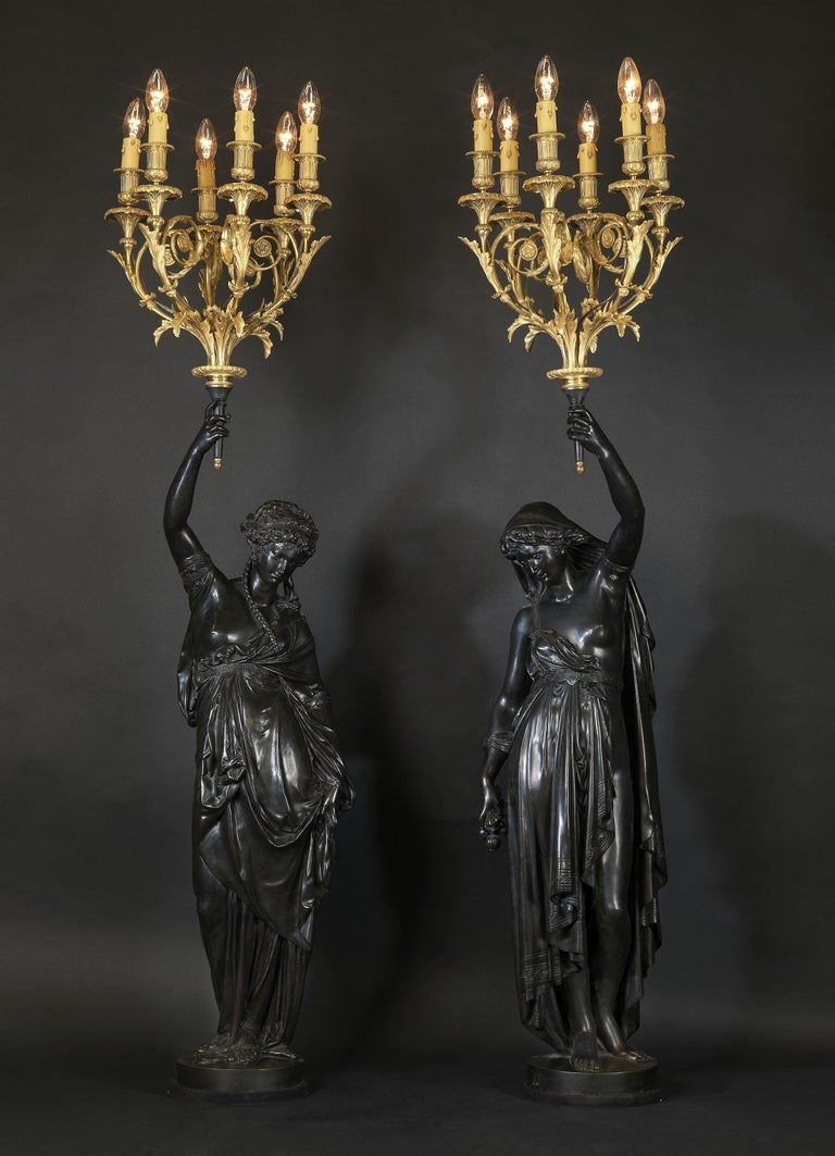 A fine pair of bronze figural torcheres by Albert Ernest Carrier-Belleuse. The torcheres modelled as classical female figures with torches held aloft. 