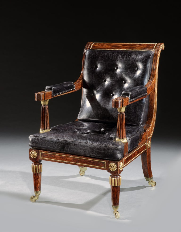A superb pair of George IV simulated rosewood and Ormolu mounted library armchairs of large scale. The scroll over backs with beaded ormolu panels above rectangular seats with fluted arms, mounted with lotus leaf Ormolu, above turned legs with