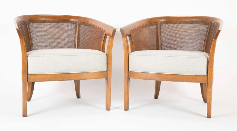 A pair of walnut Edward Wormley designed armchairs produced by Dunbar. Cain sides and backs with Rogers & Gofigon cushions.