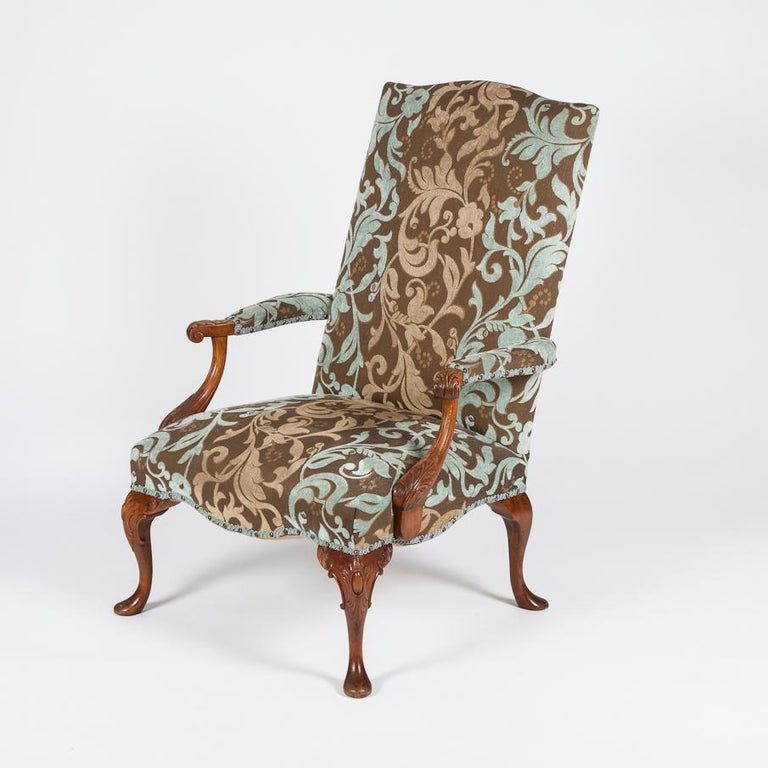 A pair of carved beech high back open armchairs in the style of the early 18th century, with detailed cabriole legs and pad feet.