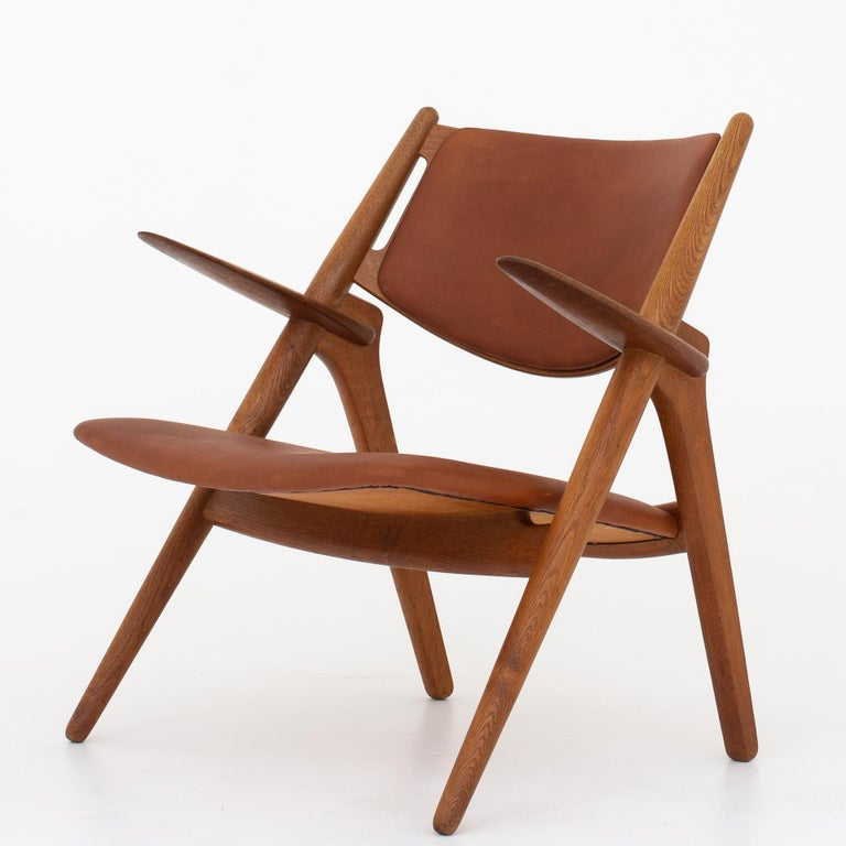 Two CH 28 - 'Sawbuck' easy chairs in patinated oak, reupholstered in Dunes Cognac leather. The leather has been treated with leather grease. Maker Carl Hansen.