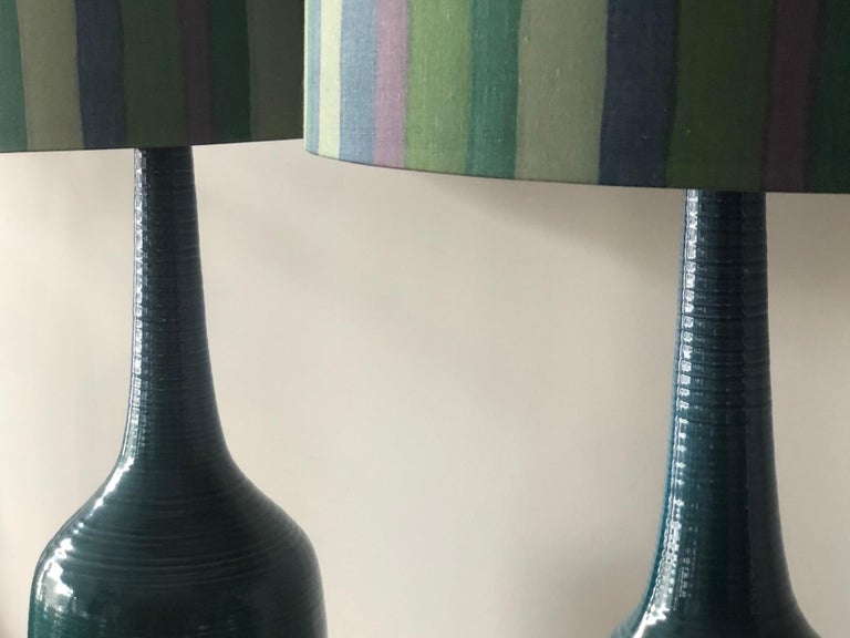 A pair of turquiose ceramic lamps with original striped shades! Greener hue changes to blue towards the top of the lamps, vintage circa 1960s. Total height with shades 40