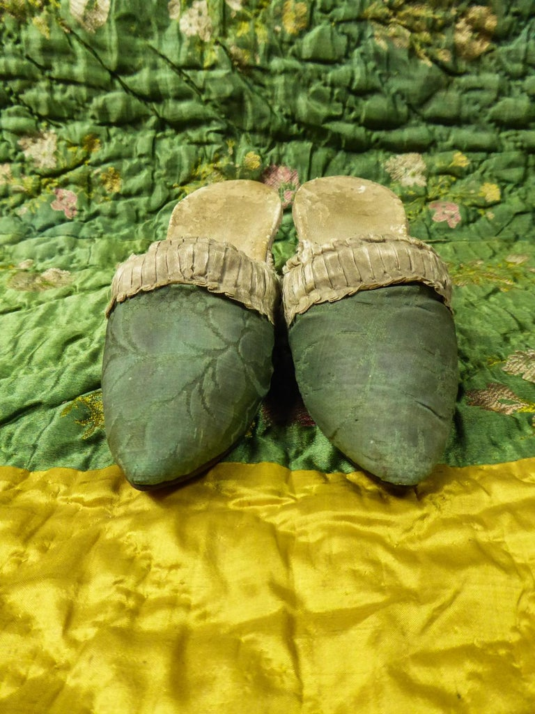 Circa 1750 France  Rare pair of shoes with spool heels for 10-14 years old child and dating from the end of the Louis XV period. Curved bulging soles typical of the Louis XV period and vamp in ecru linen covered with green silk damask and adorned