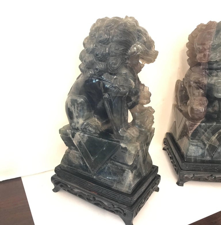 A pair of carved green quartz foo dogs with wood bases. The original pair, one male, one female in a darker variegated quartz, circa 1920.