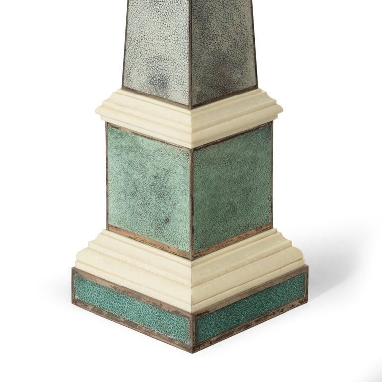 A pair of contemporary grey and aquamarine shagreen and obelisks, the square section pedestals with two stepped ivorine plinths, all with silver edging.   English, circa 2010.