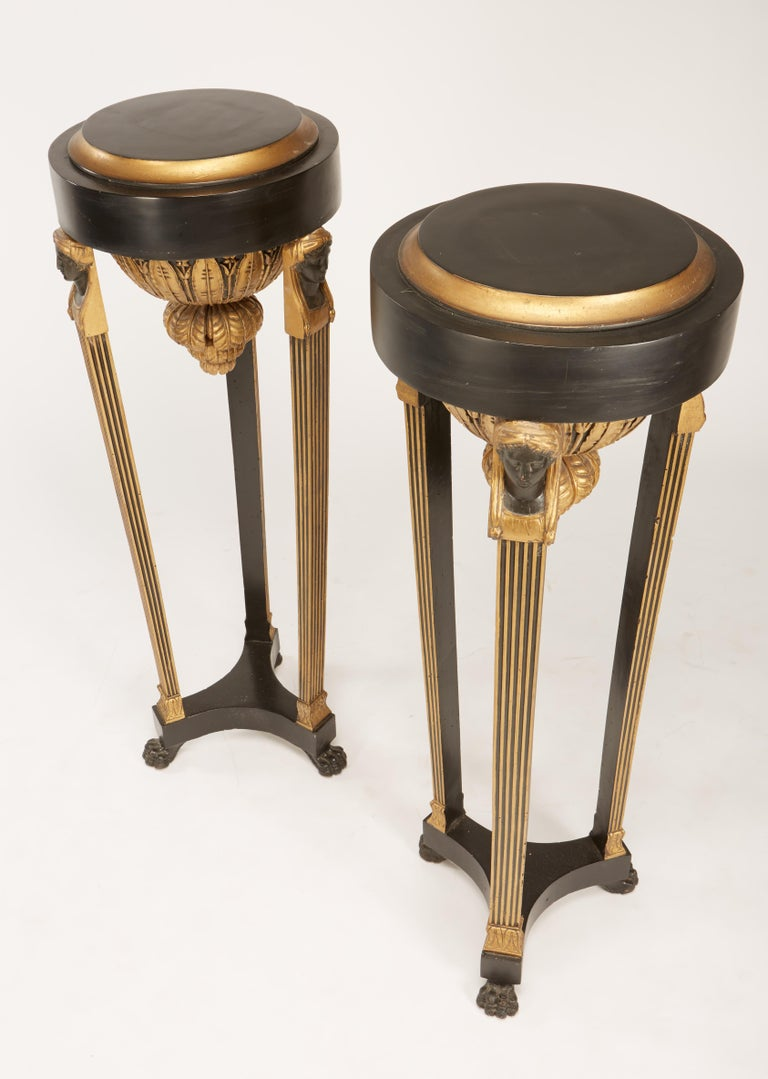 A fine matching pair of Continental Italian neoclassic black painted and parcel-gilt torcheres having urns with female bust on top of fluted legs on paw feet. Later tops, top diameter is 13.5
