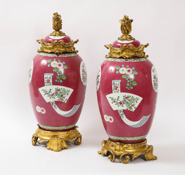 A fabulous and large pair of 19th century Louis XVI style doré bronze mounted Chinese porcelain rooster red ground covered jars/covered vases. The porcelain is of a red ground with hand painted enamel decorations of Chinese roosters, parrots,