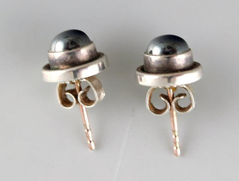 A pair of ear studs in sterling silver by Georg Jensen with cabochon cut hematite. Stamped. In very good condition. Diameter: 9 mm.