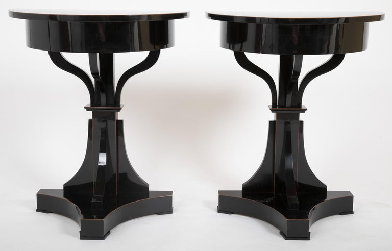 An interesting pair of 1830s Biedermeier demilune tables. Ebonized with mahogany tracery stringing.