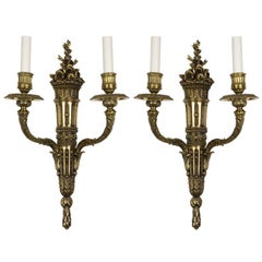 A pair of finely cast two arm brass sconces with flo