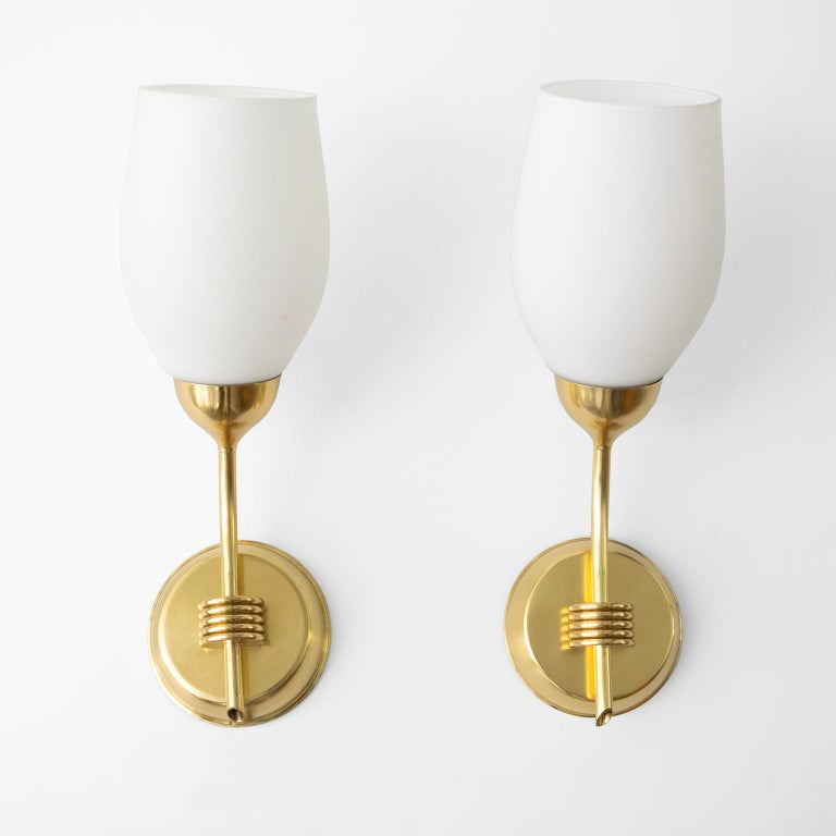 A pair of Finnish Mid-Century Modern polished brass and opaline glass sconces. Newly polished and rewired for use in the USA with standard base sockets. Unmarked attributed manufacturer Idman Oy. 