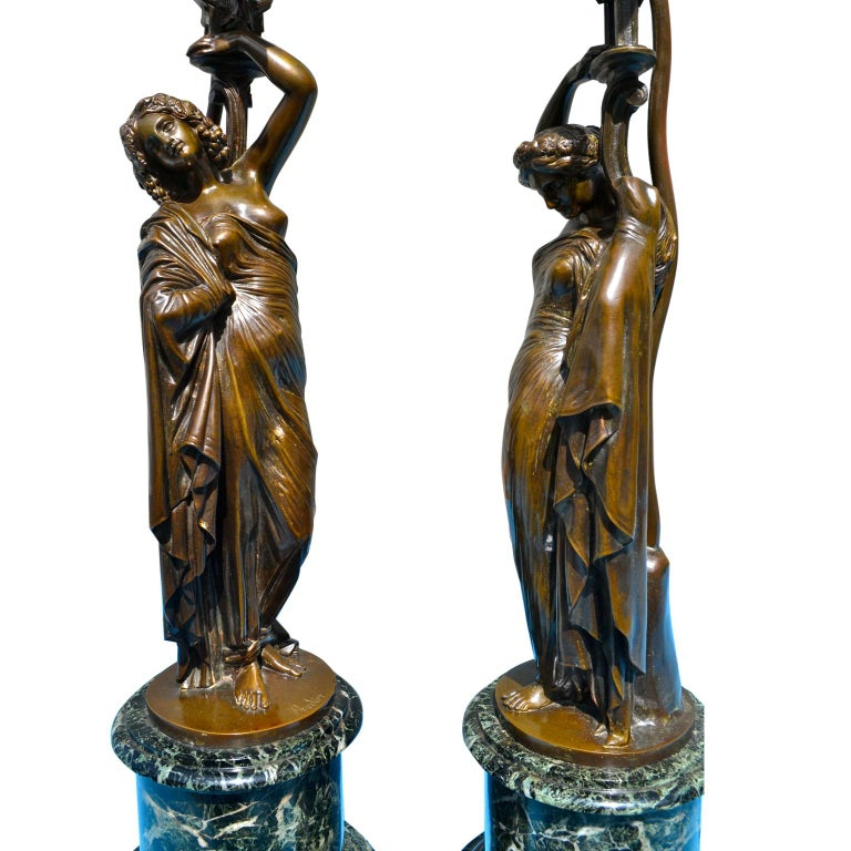 A beautifully cast pair of French 19th century neoclassical patinated figural bronze nine arm candelabra after a model by Jaen Jacques Pradier They are signed J. Pradier and were converted into lamps in the 20th century. Each candelabra is cast as