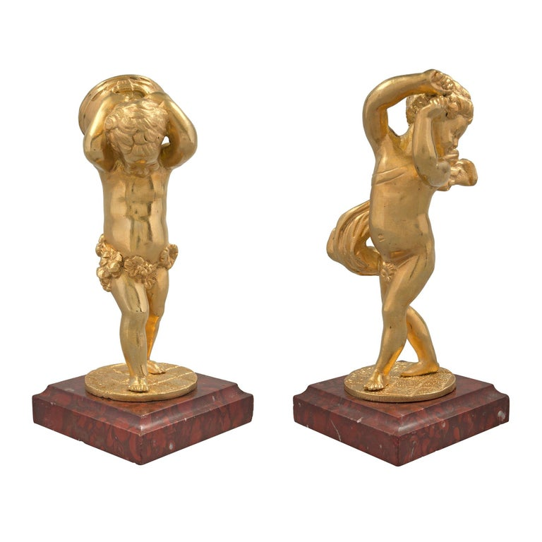 A charming pair of French 19th century Louis XVI style ormolu cherub signed statues. The pair are raised by ormolu bun feet below a square Rouge Griotte marble base with mottled border. Above are the sweet ormolu cherubs, one lifting a drum behind